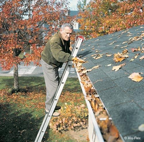 Elder Man On Ladder Cleaning Gutter Leaves in Autumn